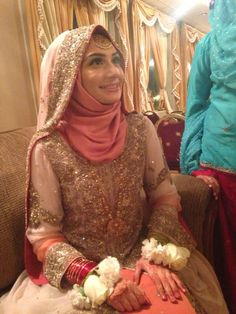 Bride in hijab wearing coral link and cream white. Makeup by Saleha Abbasi