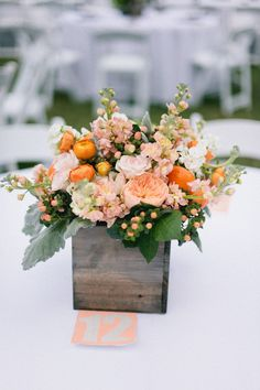 Table centres in a wooden box with a peach, apricot and orange colour theme. Photography by pinkhedgehogphotos.com