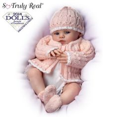 So Truly Real® fully poseable newborn baby doll by award-winning doll artist Marissa May has RealTouch® vinyl skin and wears a knitted outfit.