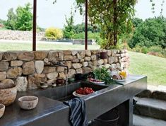 cuisine d'été rustique noire à crédence en pierre naturelle et à abri en paille