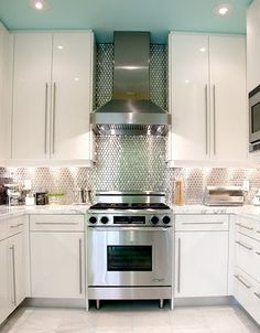 """""""#StandardPaint""""  Stainless Steel mosaic tile backsplash and the white cupboards give this kitchen a very modern look. I find the baby blue ceiling dreamy and the flush mount light fixtures are a great accent to the room."""