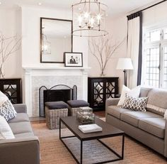 This is a fantastic layout. I'd like to see some antique glass and aged silver along with the black white and gray color palette. For example the coffee table and side cabinets in white. I'm also loving that fixture.