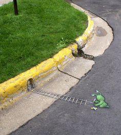 David Zinn street art. Green alien (Sluggo) drawing train tracks on the street curb