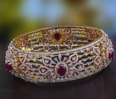 A broad diamond studded 18 karat gold bangle etched with different motifs all over and studded with few oval shaped rubies to highlight the design. Plain Gold Bangles, Ruby Bangles, Gold Bangles Design, Bridal Bangles, Gold Earrings Designs, Ankle Jewelry, Hand Jewelry, Antique Jewellery Designs, Indian Jewelry Sets