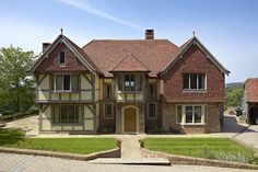 Manor house frontage with jettied gable to left hand side and brick and tile hung wing to the left hand side. Tudor House Exterior, House Exteriors, Oak Framed Buildings, Clad Home, Oak Frame House, Self Build Houses, Stone Houses, New Home Designs, House Front