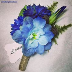 A rustic, nature/forest themed boutonniere containing a light blue delphinium bloom, cobalt blue cornflower/bachelor buttons, a lisianthus bud, fern, mini pinecones, and a jute wrapped stem. Design: Something Floral / Something Spectacular. Photo: Urban Fire Studio. #blue #boutonniere #weddingflowers #buttonhole