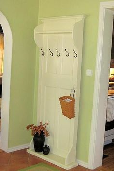 Coat rack out of an old door. Clever way to expand a small space without permanent construction. Awesome for an apartment -- take it with you!    WOULD look awesome painted with milk paint & wax.