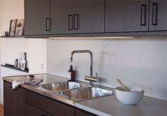 Hitta hem - Kista Torn, svart kök, stänkskydd i ljusgrå laminat