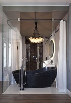 taupe bathroom with black freestanding bathtub and chandelier Source by