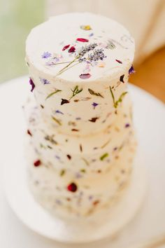 A white wedding cake provides the perfect canvas for a minimalist sprinkling of flower petals and pressed flowers. We see this cake served at a rustic-chic wedding or vintage tea party wedding. Photo via Whimsical Wonderland Weddings .