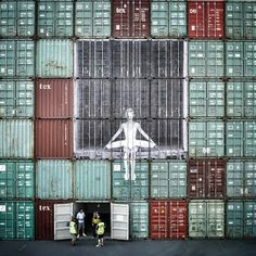 Bird Ballerina Street artist JR has once again found a creative canvas for his latest wheat paper installation. In Bird Ballerina, a ballerina is sitting behind a set of bars like a caged bird, waiting to be set free. The beautifully sad image is wheatpasted across nine shipping containers at the Port Le Havre in France.