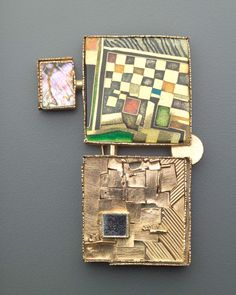 WILLIAM HARPER    RAJ COLLAGE   Two irregular squares joined with a gold disk and a pin, with a projecting rectangular drop set with mother-of-pearl. The proper right square is decorated with multi-colored cloisonne enamel; the proper left square is textured and layered rose gold with a piece of mirror glass and plastic framed in gold. Squares are backed in engraved silver. Two yellow gold pinstems. Boston Museum of Fine Art