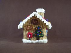 Every part of this Gingerbread House is covered with knitted treasures. Traditional sweets line the snowy roof and between the doors and windows there are more treats as well as a snowman and a Christmas tree.