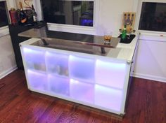 "IKEA hack - drinks bar using ""Expedit"" shelving units and a raised counter on ""Capita"" brackets; this is so cool! I would skip the frosted glass & LED lighting but I love the raised counter and the modular storage."