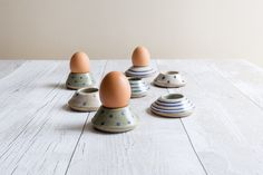 A gorgeous way to enjoy your dippy egg.   I made these sturdy little egg cups on my wheel using stoneware clay. Once shaped, they were dried, fired to 1000 degrees, decorated and glazed, then fired again to 1240 degrees.   Individually decorated with under glaze and then painted with a pale sea green or white semi-opaque glaze which lets the natural beauty of the clay shine through.