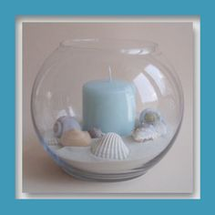 fish bowl with sand, shells, and candle