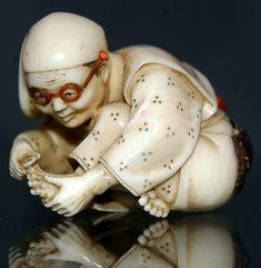 Personnage portant des lunettes et se coupant les ongles de pied.  Netsuke ( 根付 ) en ivoire