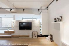 由文化石砌成的電視矮牆,串聯起後方架高的寢眠空間,讓光與空氣在此相遇流動。