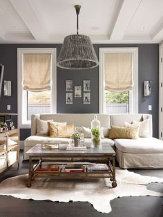 via grey decor / Gray and white living room. Eclectic feel with the white animal hide rug, industrial trolley coffee table, unique chandelier, and lovely cloches. Looks so warm and inviting even with all the cool colors.
