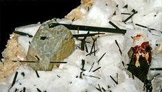 Leucosphenite, Na4BaTi2O2[B2Si10O28], Manganoneptunite, Aegirine, Petersenite-(Ce), Microcline, Poudrette quarry, Mont Saint-Hilaire, La Vallée-du-Richelieu RCM, Montérégie, Québec, Canada. Fov approx 2.2 x 1.3 cm. Leucosphenite (about 8 mm) in association with (reddish brown) manganoneptunite. MOB coll.