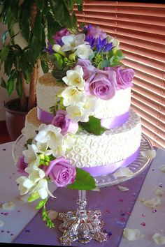 White wedding cake with purple bow and flowers made by Sugarfix Cakes