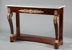 A beautiful French early 19th century Empire mahogany veneer console, consisting of two straight legs in the back and two swirl shap legs in the front, ending with gilded bronze...