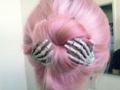Alternative pink pastel hair. Bun with skeleton hands.