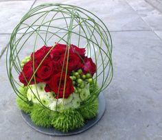 Modern grafstukje met rode rozen
