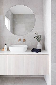 Clean lines and large format grey tile covers the floor and walls. A round frameless mirror hangs over a white sink with brass wall mounted bathroom sink faucet. The flat paneled vanity is wall mounted and has a thin white countertop Bathroom DOT + POP Bathroom Interior, Small Bathroom, Wall Mounted Bathroom Sinks, Tile Covers, Bathroom Decor, Round Mirror Bathroom, Bathroom Design, Wall Mount Faucet Bathroom Sink, Tile Bathroom