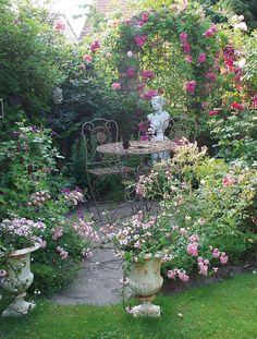 Die prachtvolle Rosen stehen in voller Blüte und wölben sich über den klassichen Roosenbogen. Die Eisenmöbel haben bereits Patina angesetzt und verstärken den nostalgischen Charme, den die violetten Rosenblüten verströmen. Zwei antikisierte Amphoren begrenzen den Zugang zur schattigen Terrasse wie zwei florale Wächter. Über allem wacht die Büste einer geradezu ätherischen Schönheit.Foto: W&G/Elke D.