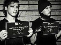 Twenty One Pilots' singer Tyler Joseph and drummer Josh Dun posing with BL/ind id's for a photoshoot