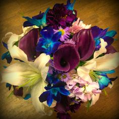 A beautiful bridal arrangement featuring purple calla lilies, blue orchids, white lilies and more! Created by our store in Grande Prairie, AB. #wedding #flowers