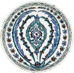 AN IZNIK POTTERY DISH, OTTOMAN TURKEY, CIRCA 1585 circular hollow, based on a small pedestal, ceramic siliceous painted polychrome decoration on a background of white slip under a transparent glaze, concentric pattern of hyacinths, saz leaves and berries surrounding a mandorla; diam. 29.5 cm 11 1/2 in.