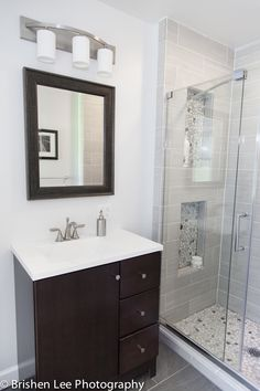 Two shower nooks with marble pebbles and horizontal grey porcelain tiles. Modern bathroom renovation. Espresso vanity and bathroom vanity mirror.