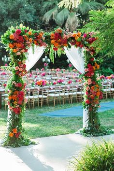 Pink and orange roses and vines bedeck a chiffon floral arch at a Disneyland wedding