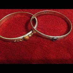 Silver Bangle Bracelets by BCBG. A set of 2 Bangle Bracelets by BCBG.  One has a brown rhinestone and the other has a blue rhinestone. BCBGeneration Jewelry