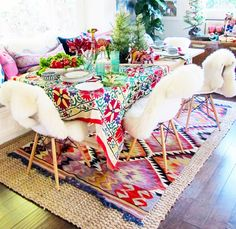 colourful table setting with an aztec kilim rug and sheepskin chairs.
