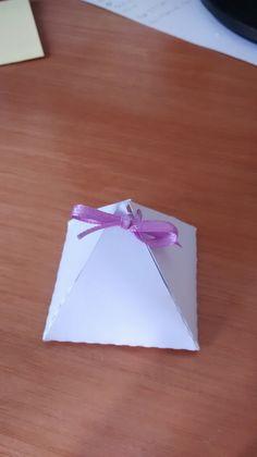 Caixinha piramide em papel branco 180gr com cetim, podendo ser colorido ou em papel brilhoso (orçamento a parte). <br>Tamanho: base 4cm altura 4cm <br>Tamanho: base 5,3cm altura 5,3cm (orçamento a parte)
