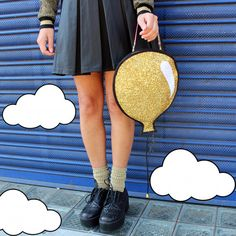 A fun balloon shaped clutch handbag. The 2D balloon is made from a bright yellow glitter fabric, bound in black satin and lined in black silk