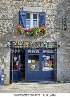 ERDEVEN, FRANCE - JULY 8, 2012: Photo showing traditional bakery in the city of Erdeven in Brittany. Typical stone wall facade and blue colored doors and windows. by goodcat, via Shutterstock