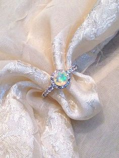 White Opal Engagement Ring Solitaire in Halo by , $189.00. A large faceted round white opal in a white topaz halo - a celestial combination! New favorite in   , this solitaire-halo ring w/ 10K WG head goes with many  bands or worn along. October  & a 14th  . Opal is said to bring love, loyalty & peace; reflects the mood of the wearer. More: