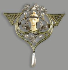 An art nouveau diamond, pearl, green enamel, platinum and eighteen karat gold pendant brooch, Georges Fouquet, circa 1900  the carved ivory female face accented by a floral motif of rose-cut diamonds and pearls, further framed by a plique-à-jour enamel openwork surround, suspending a pearl, with chain; signed G. Fouquet, reference #5572. length: 13 7/8in.
