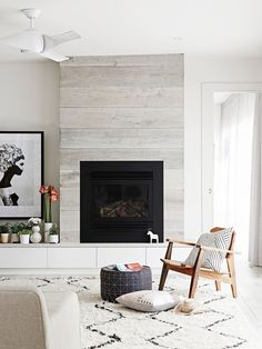 Living room: pale oak timber panelled feature wall, fireplace, white custom joinery drawers, cream rug with black zig-zag pattern, modern white ceiling fan, timber armchair with black-and-white line-art cushion, beige sofa, pale limewashed timber floorboards, round navy geometric-print ottoman/pouffe