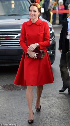 Carolina Herrera red coat is worn by The Duchess of Cambridge on her tour of Canada. She is wearing bordeaux Tod's fringed leather pumps. It is the fifth day of the tour and she is in Whitehorse, Yukon territory of Canada.