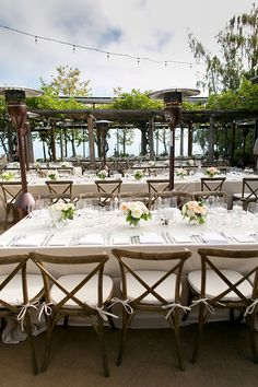 An outdoor reception with cross-back chairs | @allymagdaphoto | Brides.com