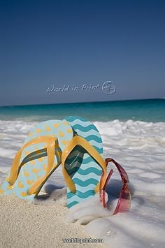 Two mismatched beach flip-flops with red sunglasses in the surf on a Caribbean beach.  Copyright © Donald Nausbaum
