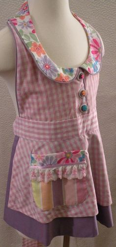 Great for Gardening, cooking, or just playing. This is a Kandyce Kreations Little Lady apron. It is a layered apron with a collared bodice and gathered back neckband. It has a mock button front, an over apron with matching waist band and ties, an under skirt, and a coordinating patch pocket. This is made in one size that fits most girls ages 3-8. The entire apron is lined. Hand or machine washable.