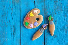 Homemade gingerbread cookies in the form of a palette with paint - Homemade gingerbread cookies in the form of a palette with paint and brushes on the blue wooden table. Space for text and selective focus
