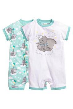 Pack de 2 pijamas: Dos pijamas en punto de algodón suave con estampado. Mangas y perneras cortas, un modelo con cierre de botones de presión en la parte delantera y el otro en un hombro y en la entrepierna.