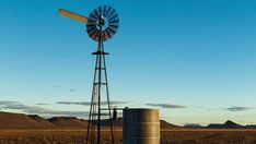 A static (medium shot) timelaspe of a windmill and old farm dam with clouds in the distance as the golden sun sets over a mountain landscape. Farm Windmill, Golden Sun, Sun Sets, Old Farm, Windmills, Mountain Landscape, Stock Footage, South Africa, Distance